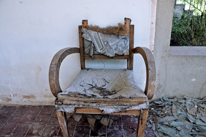 torn armchair and pile of broken glass
